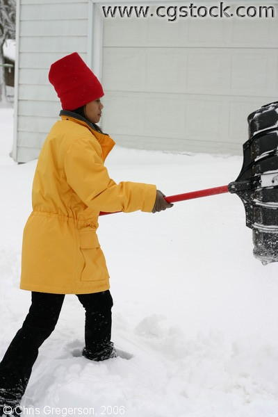 Woman Shovelling Snow in Driveway